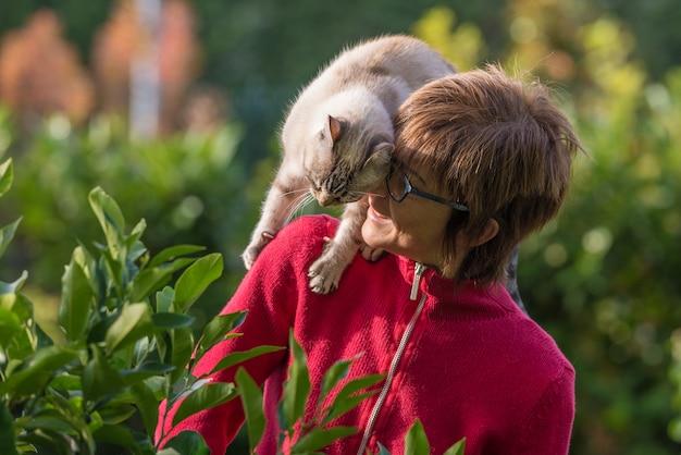 Домашняя кошка играет на плечо улыбающегося красивая женщина. наружная обстановка в домашнем саду.