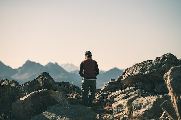 高地のロッキー山脈の風景のハイカー。イタリアのフランスアルプスでの夏の冒険、
