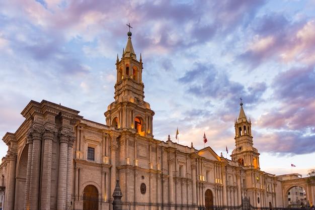 ペルーの有名な旅行先とランドマーク、アレキパの夕暮れ時の見事なカラフルな空と雲。植民地時代の大聖堂の下からの広角ビュー。パノラマフレーム。