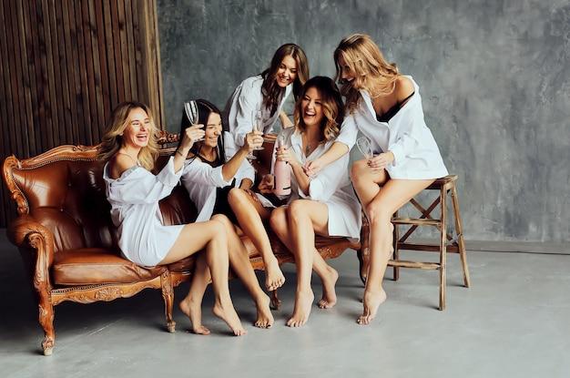 パーティーで楽しんで、笑っている女友達の多様なグループ。