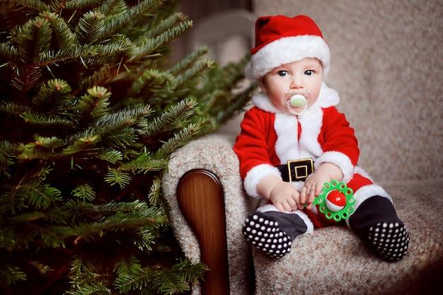 Маленький забавный мальчик в костюме санта-клауса.
