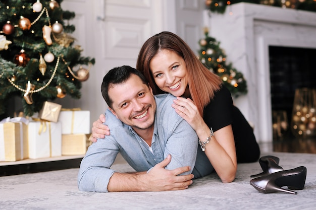 クリスマスツリーの横にある美しい若いカップル