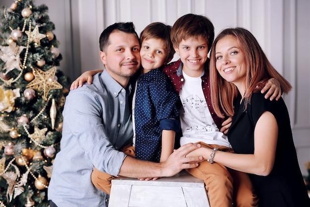 美しい大家族はクリスマスツリーの近くに家で時間を過ごす