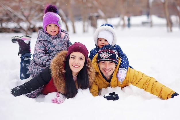 冬の幸せな家族の肖像画。両親と子供たちの笑顔。ハンサムな父親とショーパークで楽しんでいる小さなかわいい娘と美しい母親。かわいい子供たち、素敵な女性