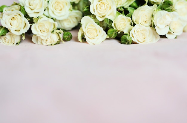 壁紙やホリデーカード用の小さな白いバラと柔らかいピンクの背景
