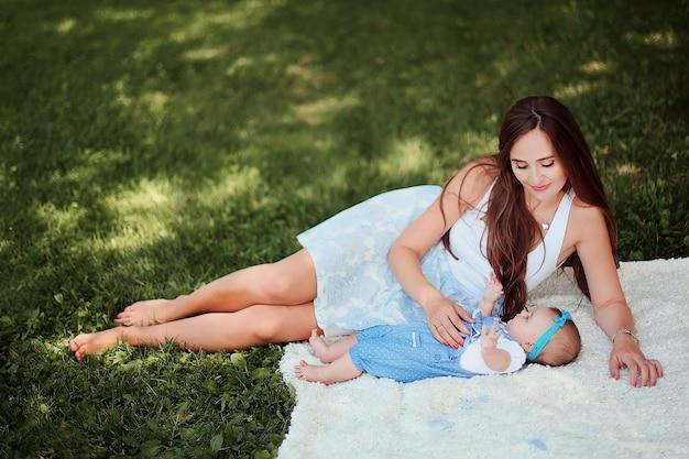 横になっていると青いドレスで彼女のかわいい赤ちゃんと遊ぶ美しい笑顔の女性。夏の公園で小さな女の子と思いやりのある母。