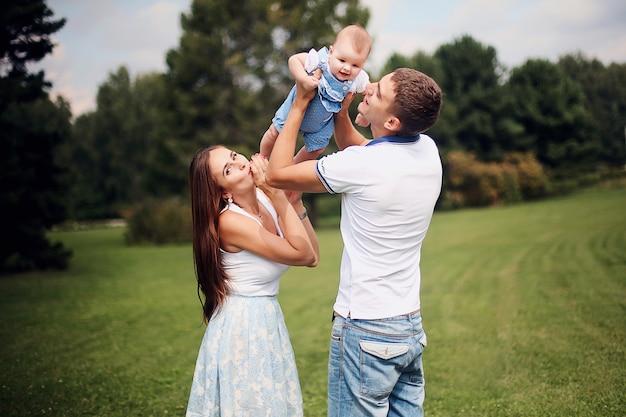 幸せな家族。笑顔の両親が子供にキスします。ハンサムな父親と美しい母親は公園で彼らの腕に彼らの小さな娘を抱いています。若い男と女。
