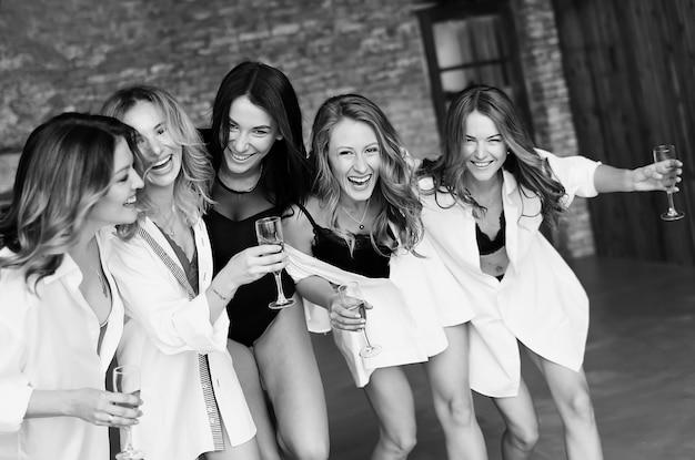 パーティーで楽しんで、笑っている女友達の多様なグループ。白い服を楽しんで美しい幸せな女性のグループ