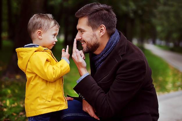 ハンサムな若い父親と一緒に遊んでいる彼のかわいい子