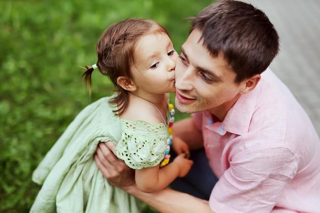 幸せな娘は彼女の父と公園で楽しんでキスします。夏の日に彼女のお父さんとかわいい若い女の子。