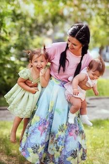 家族。公園で一緒に楽しんで彼女のかわいい娘と一緒に美しい陽気な母の肖像画。