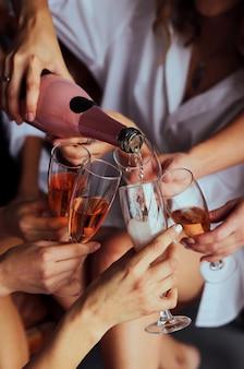 女の子はシャンパン、友達を祝い、乾杯を手に持った眼鏡を持っています。美しい女性の手。