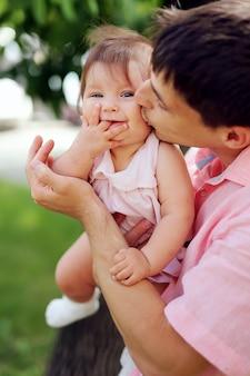 Счастливый отец и дочь, с удовольствием в парке. симпатичная молодая маленькая девочка со своим красивым мужчиной на природе. папа держит его милый ребенок