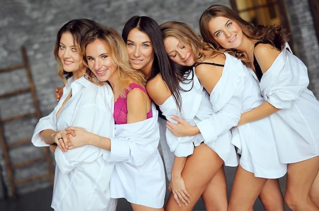 Разнообразная группа подруг, наслаждаясь на вечеринке и смех. группа красивых женщин с удовольствием в белых одеждах