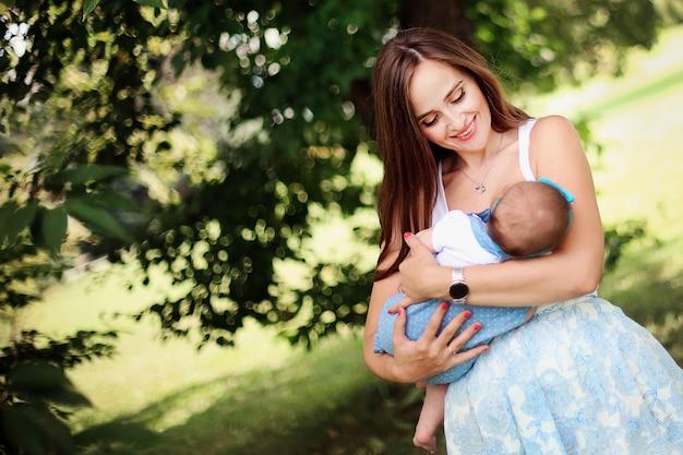 幸せな家族。公園で一緒に楽しんで彼女の娘と一緒に美しい陽気な母。思いやりのある女性は自然に彼女のかわいい赤ちゃんを授乳します。