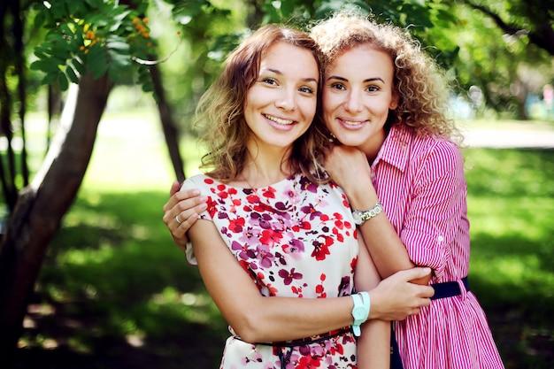 Две красивые улыбающиеся девушки обнимаются в парке летом.