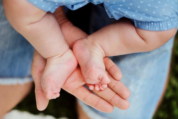 Детские ножки в руках родителей