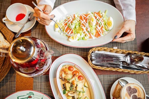 サラダ、ピザ、カプチーノ、フルーツティーのブランチ