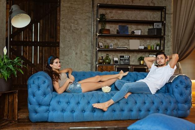 ソファでポップコーンとカップルが家でテレビを見て