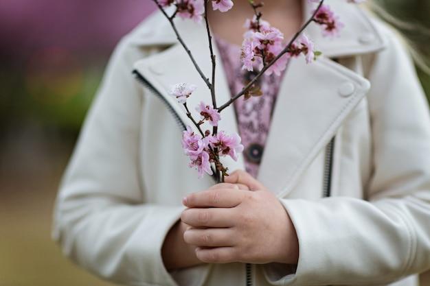 咲く花のクローズアップの枝を保持している女の子