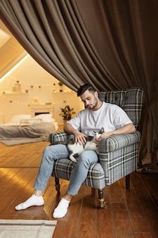 Молодой человек на стуле с кошкой