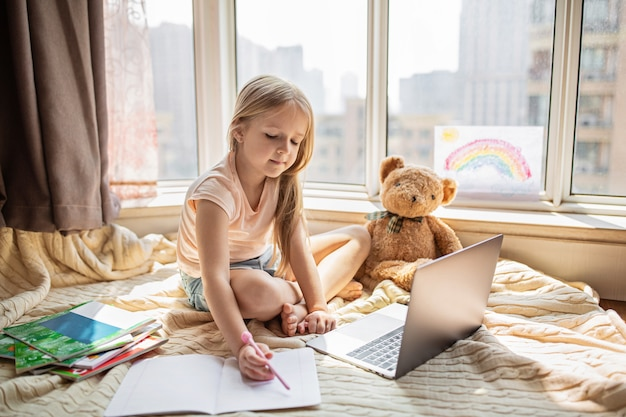 自宅でのオンラインレッスン中に宿題をしている女子高生