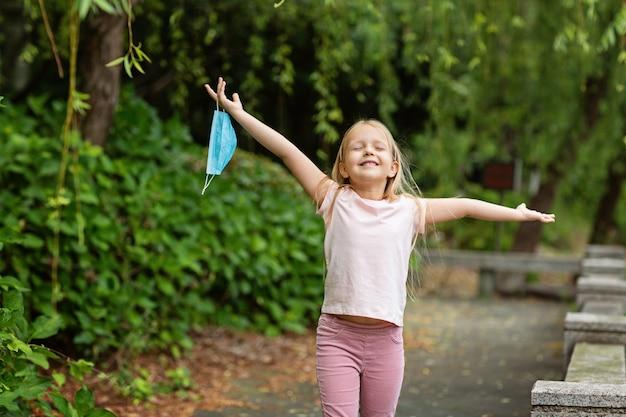 Счастливая маленькая девочка снимает защитную медицинскую маску с лица на открытом воздухе