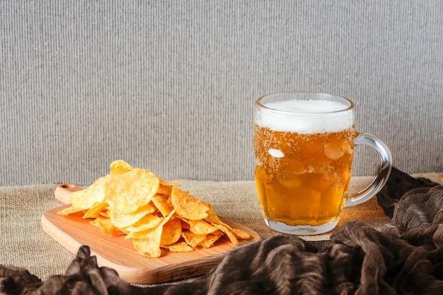 ビールのグラス、ブラウンの塩味のチップス