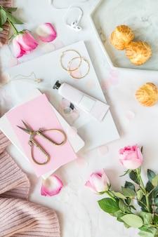 クリエイティブデスクトップアイテム:ピンクのバラ、はさみ、ヘッドフォン、ノートブック、雑誌、白で横になっているケーキ