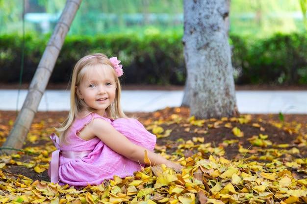 Счастливый маленькая девочка смеется и играет в осень на природе прогулка на свежем воздухе