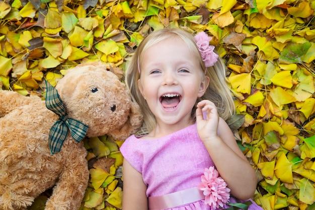 Маленькая девочка лежит на улице на опавших листьях со своим другом плюшевым мишкой