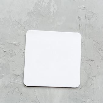 オフィスや自宅の灰色のテーブルの上の白い空白の紙のメモ帳