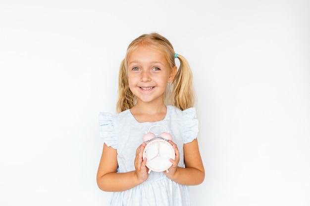 白い背景の上の目覚まし時計を保持しているブロンドの髪とかわいい女の子