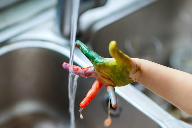 幸せな面白い子少女は塗料で汚れた手を示しています