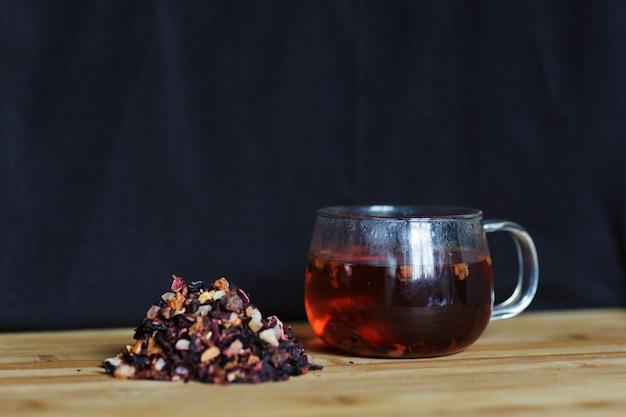 Горячий фруктовый чай в чашке на черном фоне