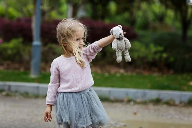 屋外の汚れたテディベアを抱いた子供