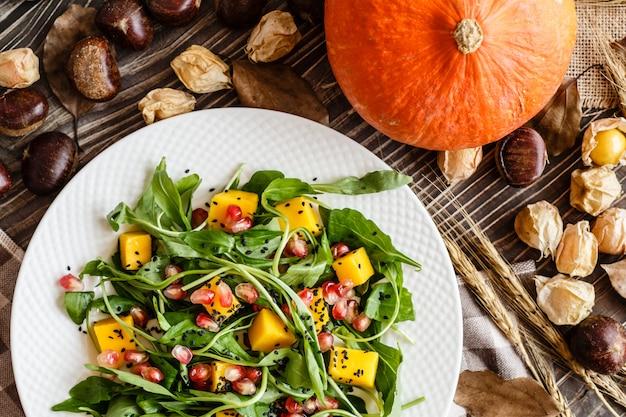 マンゴー、ローストカボチャ、ルッコラ、ザクロの種子の白いプレートの上に横たわるのサラダ。