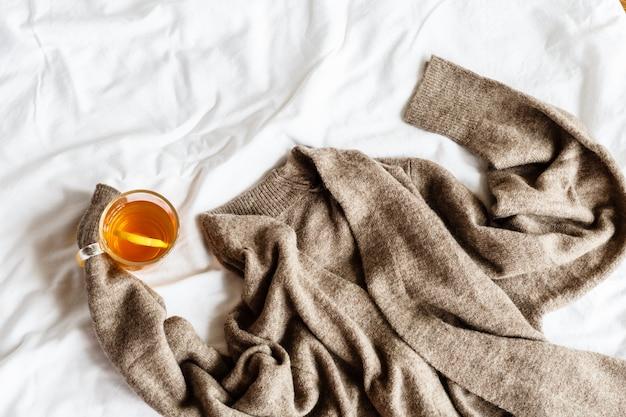茶色のニットセーターと白で横になっているレモンと紅茶のカップ。