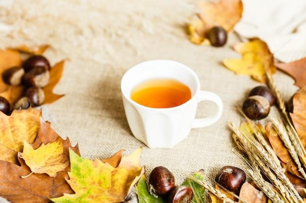Осенние листья клена, чашка чая и каштаны, лежа на коричневом.