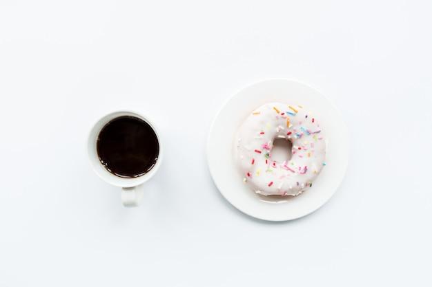 フラットレイアウトアイテム:コーヒーカップと白い背景の上に横たわるドーナツ