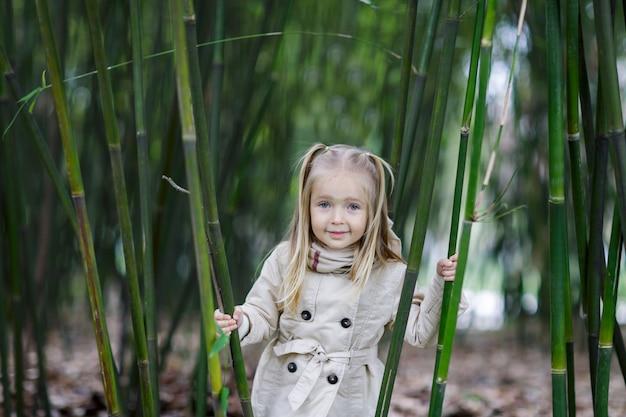Красивая маленькая девочка со светлыми волосами стоит в бамбуковом лесу и трясет бамбуком