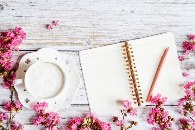 フラットレイアウトデスクトップアイテム:コーヒーマグカップ、ペン、ノート、白い木製のテーブルにピンクの花