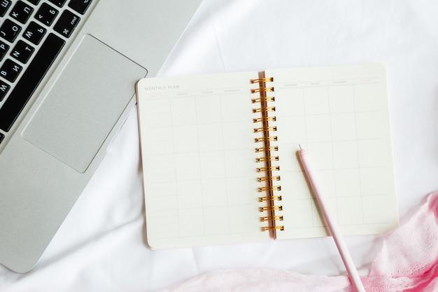 ラップトップ、ノートブック、ペンとフラットレイアウトベッドワークスペース