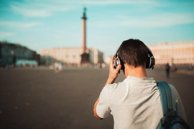 バックパックと屋外のワイヤレスヘッドフォンでスタイリッシュな若い男