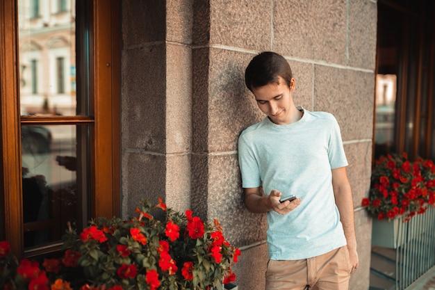 屋外の携帯電話を使用してスタイリッシュな若い男