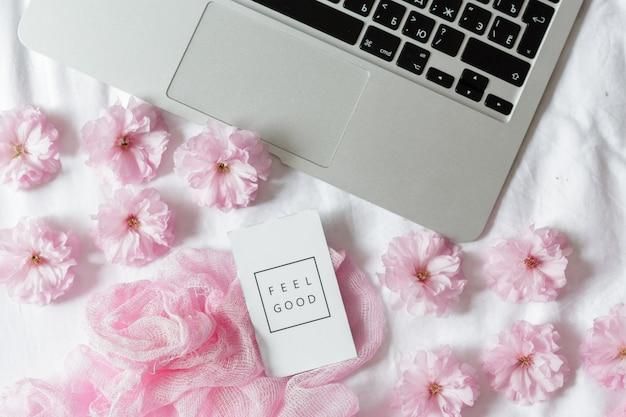 カラフルなフラットレイ:ベッドに横になっているラップトップ、桜の花、カード、布ピンク色