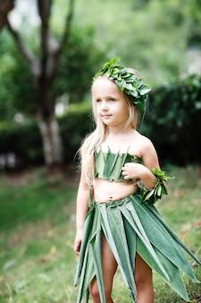 屋外の緑の草で作られたカーニバル衣装でかわいい金髪少女の肖像画