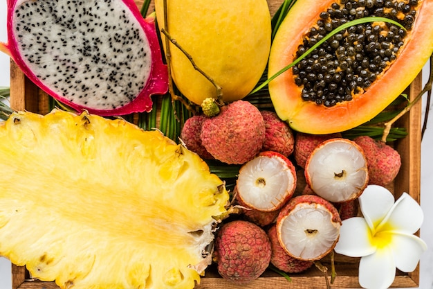 プルメリアの花と木製の箱のクローズアップで新鮮なエキゾチックなフルーツ