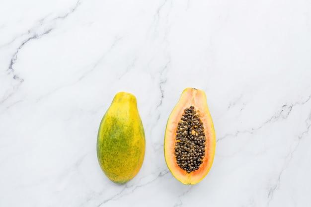 Половина свежей папайи на белом мраморе