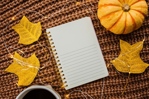 カボチャ、ノート、コーヒーカップ、茶色のニットセーターの落ち葉